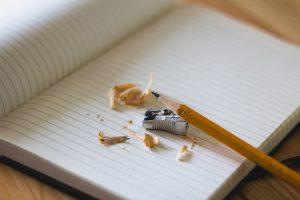 Aufgeschlagenes Notizbuch mit Bleistift, Anspitzer und Resten vom angespitzen Bleistift