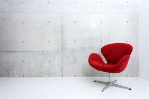 Roter Drehstuhl vor einer grauen Wand