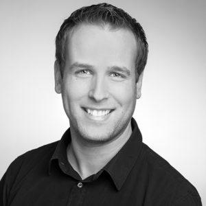 Peter Debus mit einem netten Lächeln in schwarz weiß