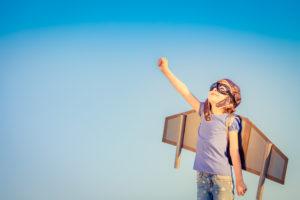 Kleines Kind mit Pilotenbrille und selbstgebastelten Flügeln schaut mit ausgestreckter Faust nach oben