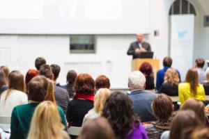 Mann hält Vortrag an einem Podium