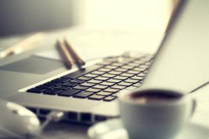 Laptop mit Tasse Kaffee
