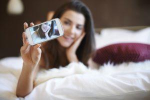 Mädchen macht Selfie auf Bett