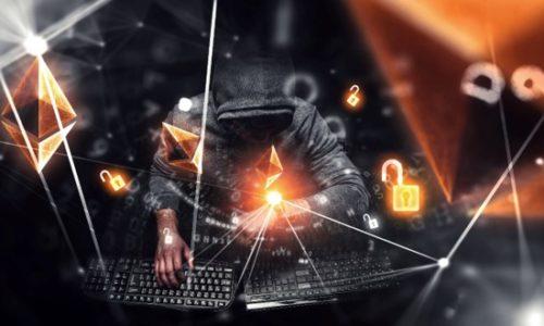 Hacker sitzt vor zwei Laptops