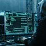 Verdeckter Hacker in einem Versteck mit dunkler Atmosphäre und mehreren Displays