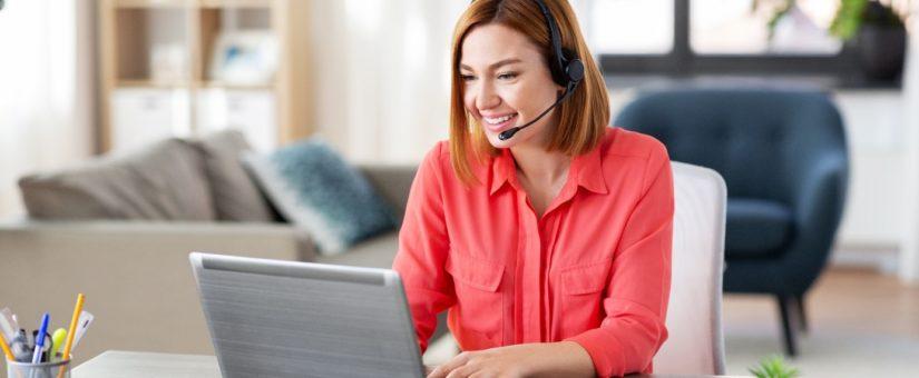 Lächelnde Frau sitzt im roten Hemd mit Headset vor dem Laptop