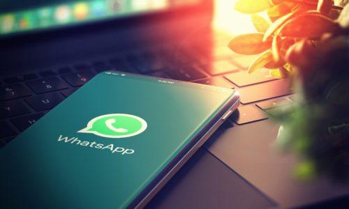 Smartphone mit Whatsapp Logo auf dem Bildschirm liegt auf Laptoptastatur