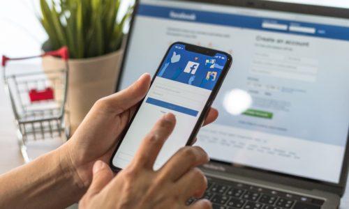 Person mit Handy in der Hand vorm Computer