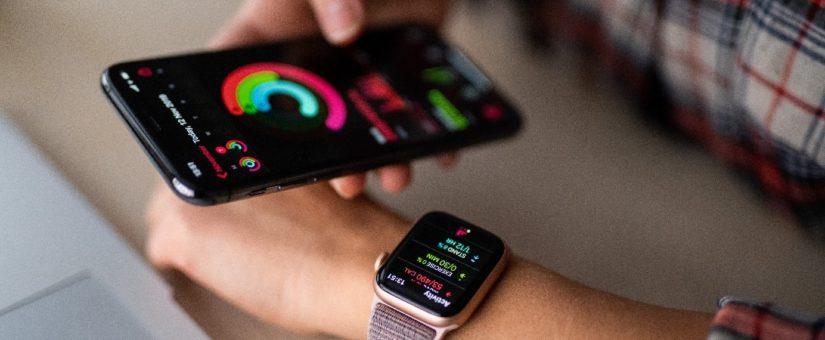 Person trägt Smart Watch und hält ein iPhone in der Hand
